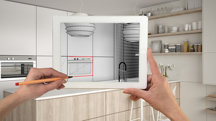 Hands holding and drawing on tablet showing modern white and wooden kitchen CAD sketch. Real finished interior in the background, architecture design presentation