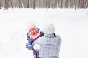 Family, childhood and nature concept - Young mother hug little daughter in the winter park
