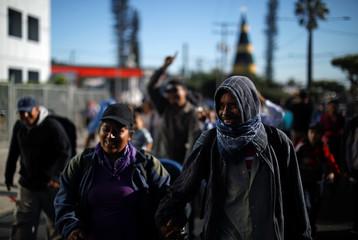 People walk in a caravan of migrants en route to the United States, in San Salvador