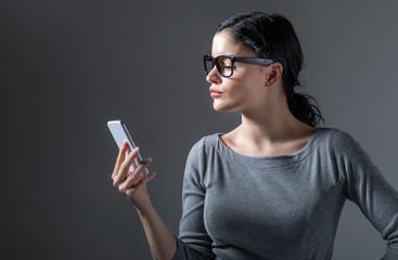 Young woman staring at her cellphone on a gray background