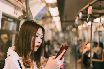 Business woman in subway using smartphone,Woman working on smart phone while traveling by train. Business travel concept.