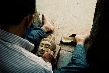 man finishing a buddha head sculpture as a part of the restoration project at the temple ruins Fototapete