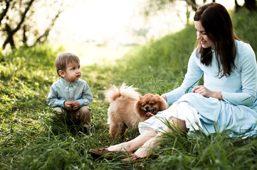 Mom and baby are playing with the dog sitting on the grass in the apple orchard