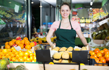 saleswoman standing behind the counter with  fruit