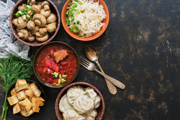 A variety of Russian food, borscht, pickled mushrooms, dumplings, sauerkraut, croutons on a dark rustic background. Top view, copy space.