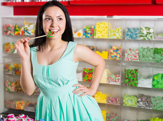 Smiling girl sucking   lollypop in  store