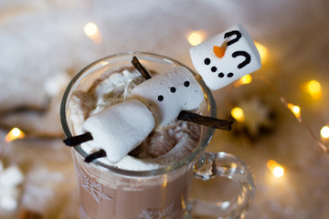 Hot chocolate with marshmallows. Fun food art with snowmen for kids during the winter time. Selective focus