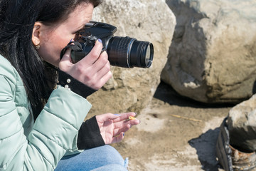 A girl in a warm jacket with a camera and a cigarette on a rocky shore taking pictures of objects