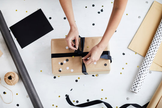 Directly above view of anonymous woman tying ribbon bow around wrapped gift box over white table with decoration stuff