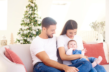 Happy young parents with their baby girl enjoy Christmas time while relaxing on the sofa. Family life.