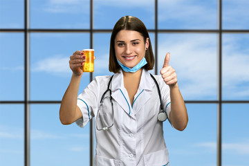 Cheerful doctor holding container of pills. Pretty smiling woman doctor gesturing thumb up on sky window background. New effective medication.