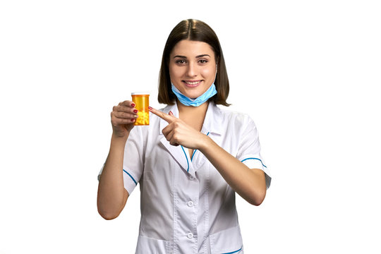 Young physician pointing on medication. Cute female doctor holding bottle of antibiotics and looking at camera over white background.