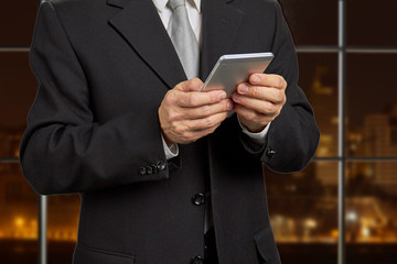 Businessman holding smartphone close up. Mature man in formal wear using his phone on evening office background. People, business, technology.