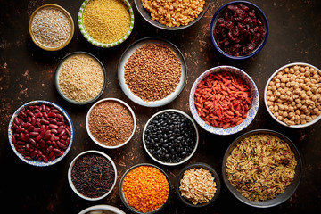 Various superfoods in smal bowls on dark rusty background. Superfood as rice, lentil, beans, peas, goji, flaxseed, buckwheat, couscous, chickpeas Top view Flat lay