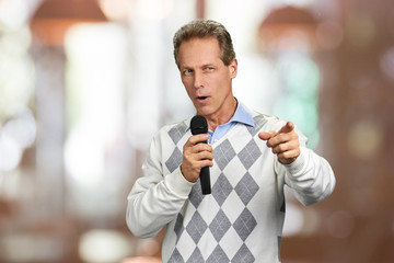 Man with microphone showing forward with finger. Man talking into microphone and gesturing. Concept of interactive discussion.