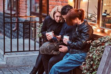 Three happy friends having a break with coffee sitting near a cafe outside.