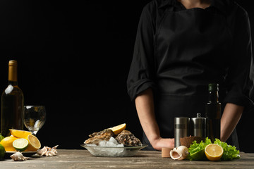 Chef with fresh oysters and a bottle of white dry wine on a dark background, horizontal photo, for seafood advertising