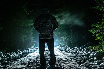 Man walks through the forest against the backdrop of a bright light