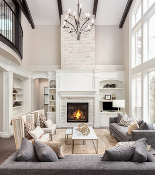 Beautiful Living Room in New Luxury Home with Fireplace and Roaring Fire. Large Bank of Windows Hints at Exterior View. Vertical Orientation
