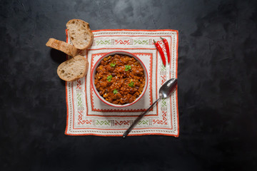 Chili con carne in bowl on dark background. Mexican/Texas traditional dish.
