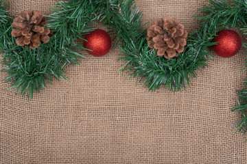 Winter holiday decoration: green garland pine cones and Christmas tree balls on burlap background