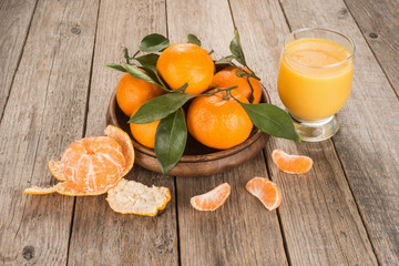 Tangerines with leaves and juice in a glass on wooden table