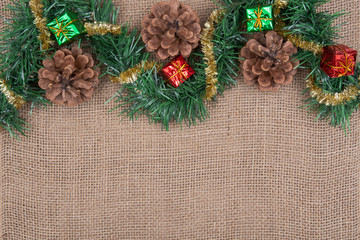 Winter holiday decoration: tinsel garland, pine cones and Christmas gift decor on burlap background