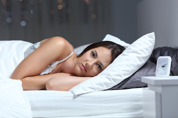 Angry woman looking at camera on a bed in the night