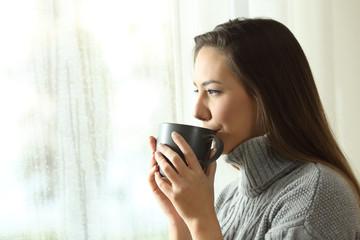 Happy woman drinking coffee looking rain through a window