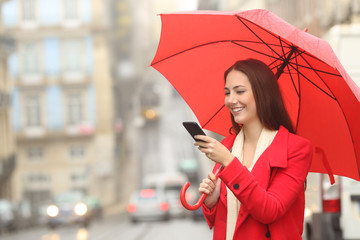 Happy woman in red using a phone under the rain