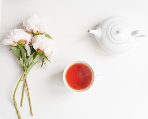 Directly above view of pale pink peonies, tea in cup and teapot on white background (selective focus)