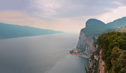 View of the Lake Garda from Terrassa Tremosine, Italy.Panorama of the gorgeous Garda lake surrounded by mountains in the summer on a cloudy day.