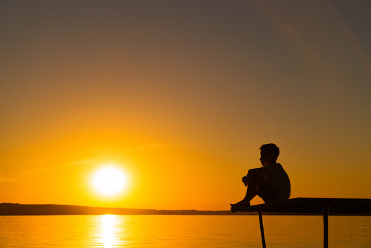 Silhouette of a little boy sitting on the bridge in river at the sky sunset. A lonely boy sits quietly and looks ahead at a beautiful view of sunset.