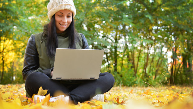 Girl in hipster with laptop in autumn park. A woman in a cap using a laptop while sitting on fallen leaves. Freelancer in the hat uses remote communication technology. Remote work. Free space