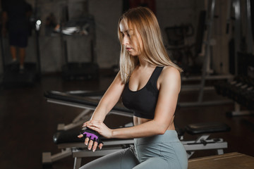 Young slender woman preparing for sports training and putting on her sports gloves in gym