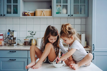 Two little girls in the kitchen sitting on the table. Wall mural