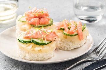 Bruschetta toast of white bread with slices of pineapple cucumber fish salmon fresh green sprouts