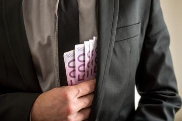 Bribery concept - businessman placing cash in his pocket
