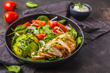 Chicken breast and avocado salad with spinach, tomatoes and Caesar dressing, dark background.