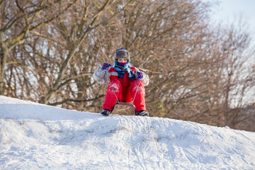 boy at the sledge on top of snowy hill waiting for riding