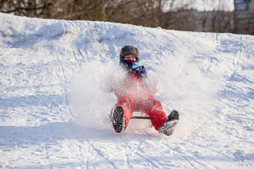 happy boy riding at the slide on snowy hill