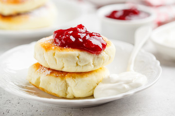Cottage cheese pancakes with sour cream and jam on white plate.