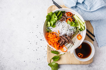 Fototapeta Bun cha salad bowl. Vietnamese rice noodle with beef and chilli vegetables salad in white bowl, copy space. obraz