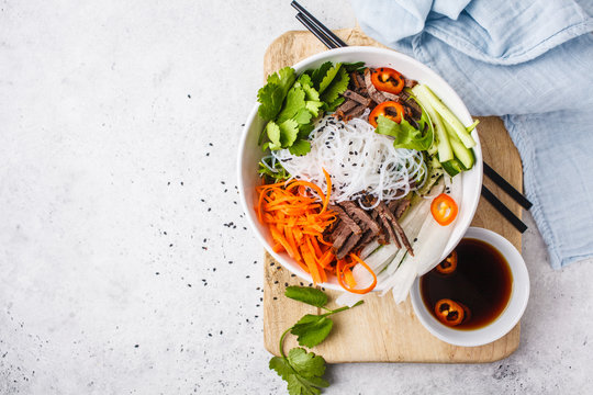 Bun cha salad bowl. Vietnamese rice noodle with beef and chilli vegetables salad in white bowl, copy space.