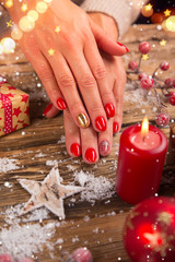 Woman with beautiful red nails on vintage wooden table