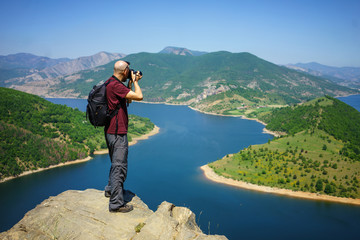 Photographer taking landscape photo in Arda river in Rhodope Mountains, Bulgaria