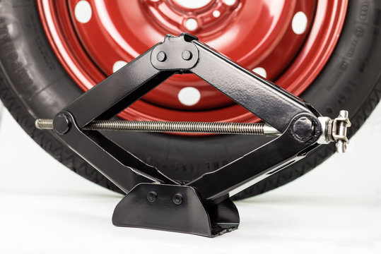 Spare car tire on steel, red rim and manual scissor car jack, isolated on a white background with a clipping path.