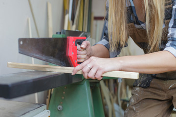 close up of a woman sawing wooden slat