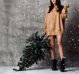 Beautiful woman with Christmas fir tree in sexy knitted sweater blouse under snow