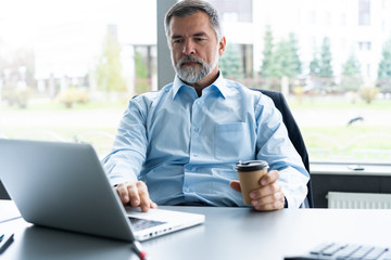 Senior businessman working on laptop computer in the office.
